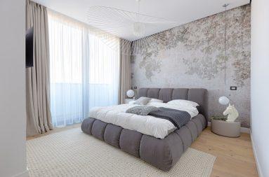 Серая кровать в спальне в светлых цветах